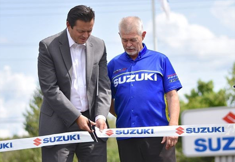 Two men cutting Suzuki ribbon at event